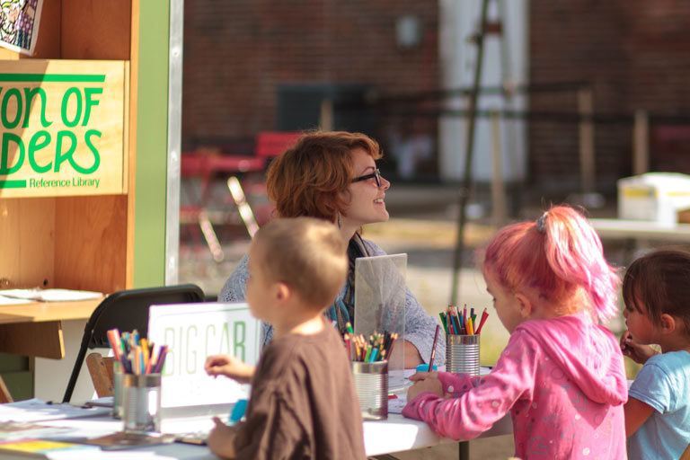 Three children draw at a table outside while a person smiles into the distance