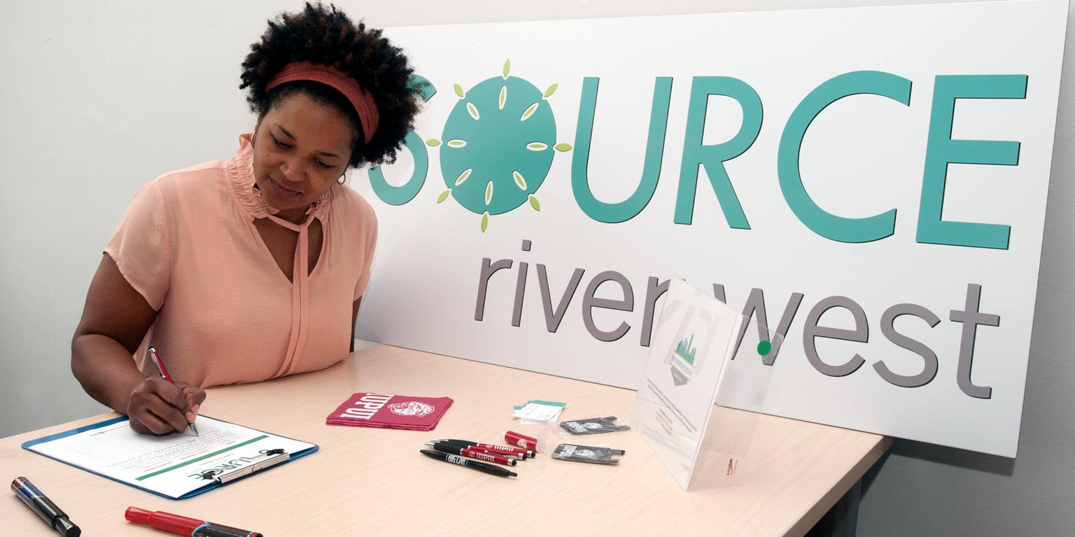 A person fills out a form at a table with a sign that says Source River West.