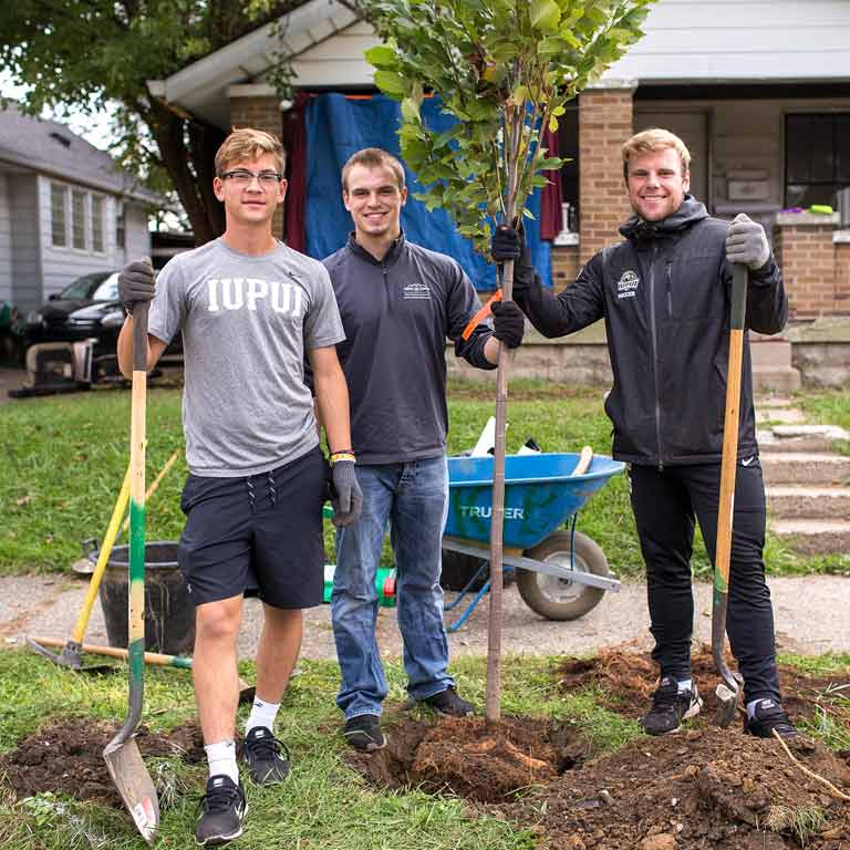 Three people stand in front of a home. Two are holding shovels. One is holding a tree. There is a hole in the ground.