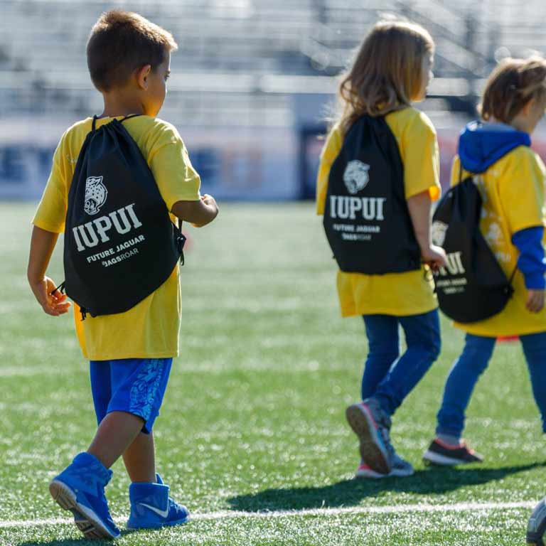 Three children in yellow shirts carrying IUPUI backpacks walk across a sports field.