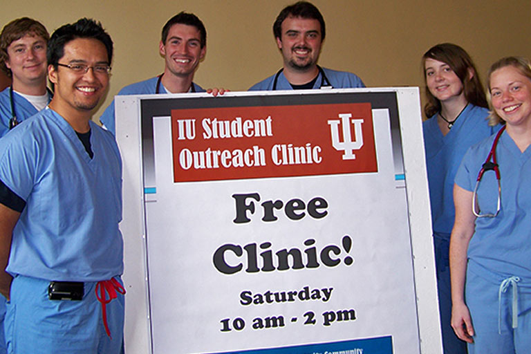A group of people in scrubs stand around a sign that says Free Medical Clinic, Saturday, 10 a.m. to 2 p.m.