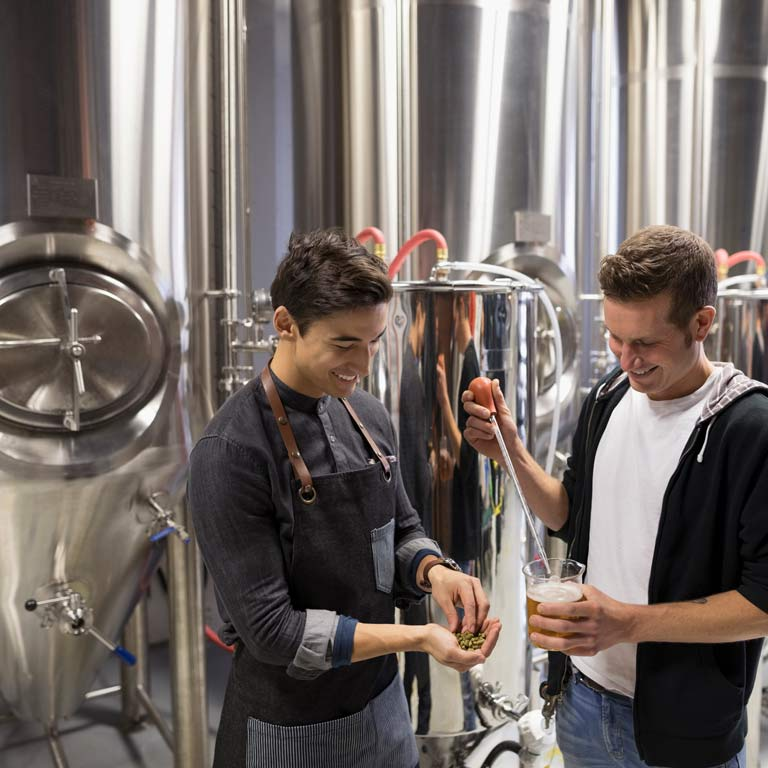 Two people stand inside a brewery. One is pouring beer from a metal tank.